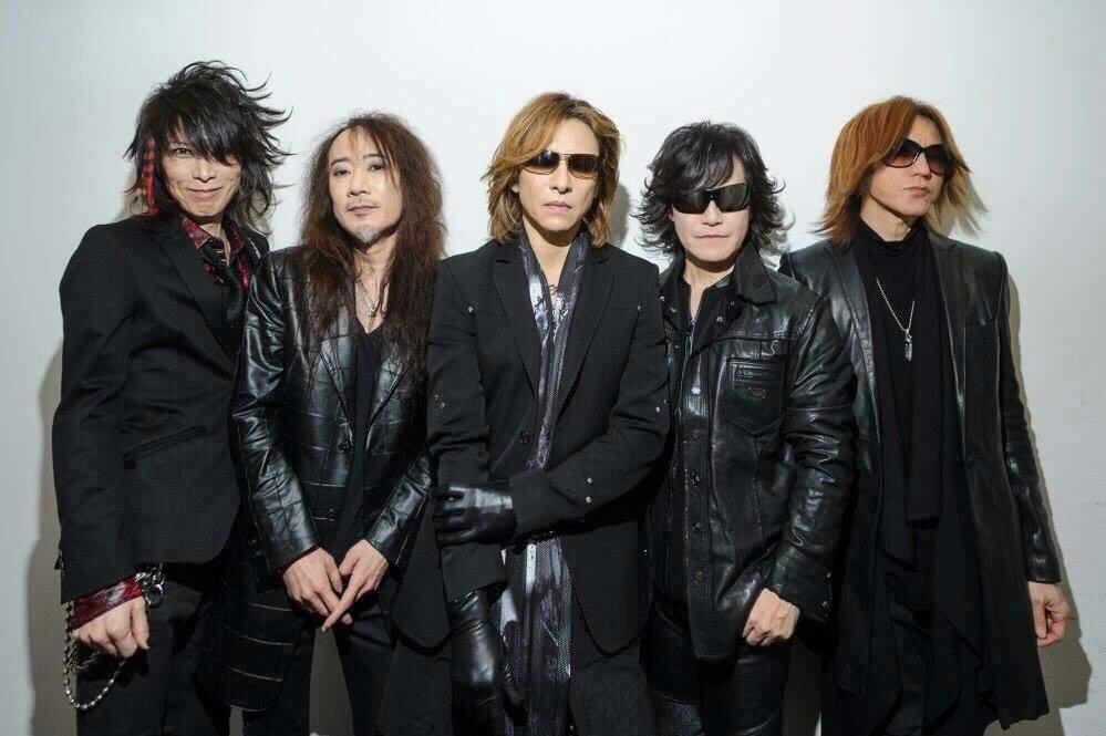全身黒い衣装に身を包んで並んでいるX JAPANの画像